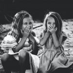 grayscale photography of two girls closing their mouths