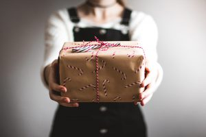 person showing brown gift box
