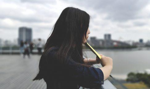 woman holding yellow envelope outside