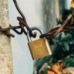 brass padlock on brown metal fence