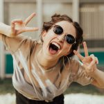 selective focus photography of jolly woman using peace hand gesture