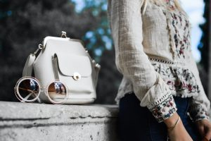 woman wearing beige and red floral top leaning on gray concrete slab with white leather bag ontop