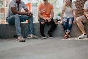 four persons sitting on concrete bench