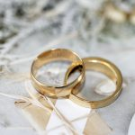 gold wedding band on white textile