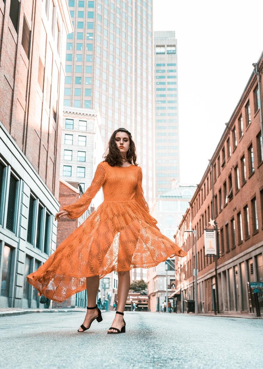 woman in orange long-sleeved dress between buildings during daytime